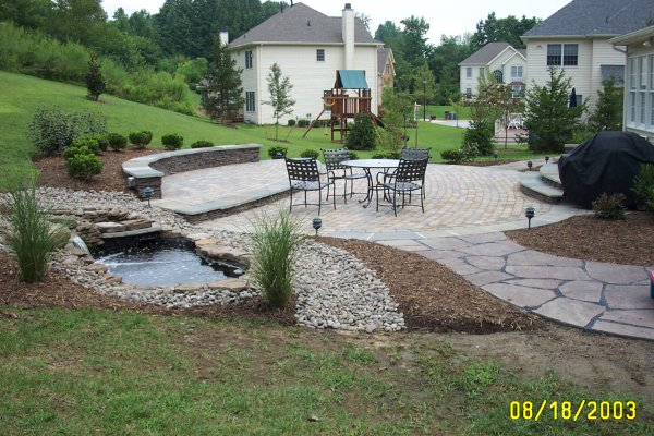STACKED STONE SITTING WALL WITH PAVER PATIO AND FLAGSTONE WALKWAY